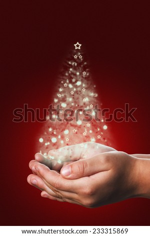 Christmas card with a shiny tree coming from a child hands on a red background, a traditional gift that Christians people use tu send their friends to congratulate them in Christmas time - stock photo