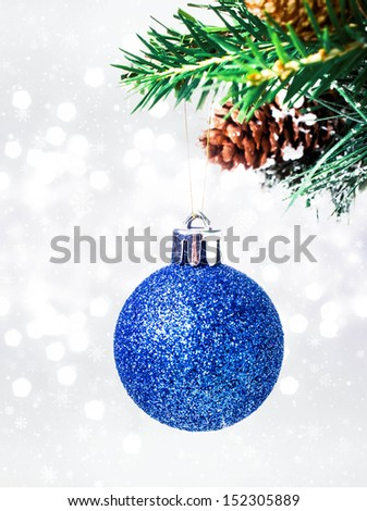 Christmas card with blue hanging ball and pine branch on Defocused Christmas Bokeh silver background with snowflakes - stock photo