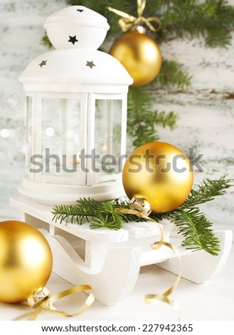 Christmas card with candle lantern and sledge on wooden background - stock photo