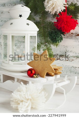 Christmas card with candle lantern, cookies and sledge on wooden - stock photo