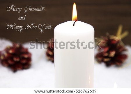 Christmas card with candles and pine cones on snow