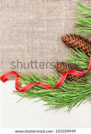 Christmas card with canvas, fir branch and pine cones on burlap