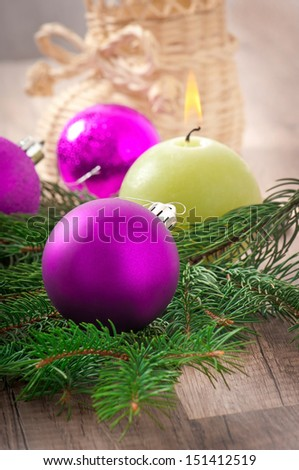 Christmas card with Christmas balls and a burning candle - stock photo