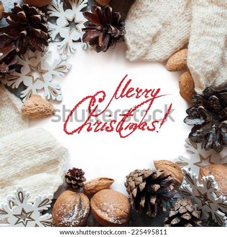 Christmas Card with Decoration Snowflakes, Pine Cones, Almonds, Mittens and Message Merry Christmas on the letter, isolated on white - stock photo