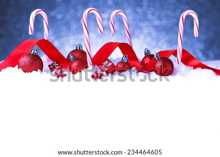 Christmas card with decorative baubles and candies on snow - stock photo