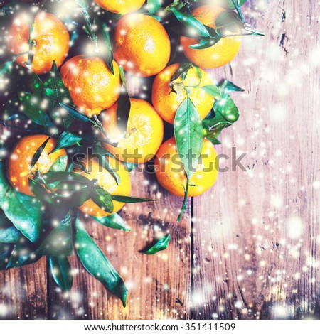 Christmas Card with festive tangerines,  snow and defocused garland lights. Xmas, New Year Background. Holiday decoration  - stock photo