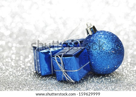 Christmas card with gifts and decoration on shiny silver background