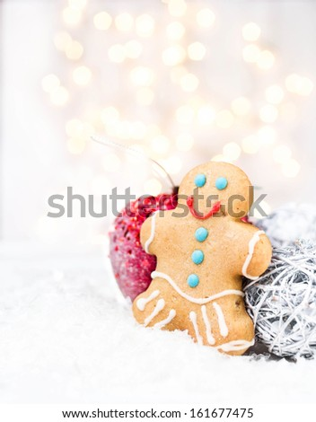 Christmas card with Gingerbread Man cookie, festive decorations and Christmas lights with copy space for greeting text.  Twinkling  red apple on white snow. - stock photo