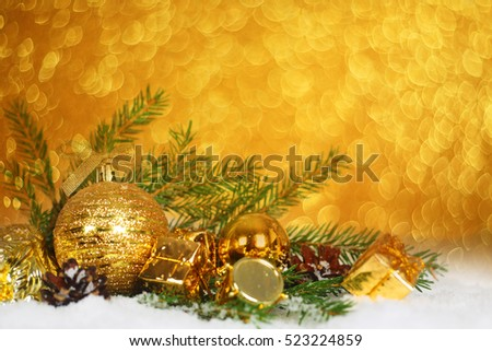 Christmas card with gold baubles and gifts on golden bokeh light background with copyspace