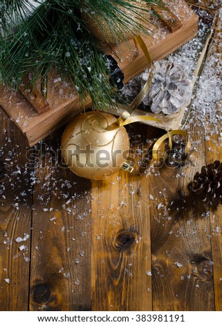 christmas card with golden baubles, cones and fur tree on wooden background - stock photo