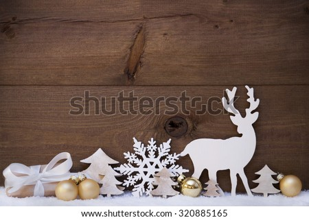 Christmas Card With Golden Festive Decoration On Snow. Gift, Present, White Reindeer, Christmas Tree, Christmas Ball, Snowflake. Brown, Rustic, Vintage Wooden Background. Copy Space For Advertisement - stock photo