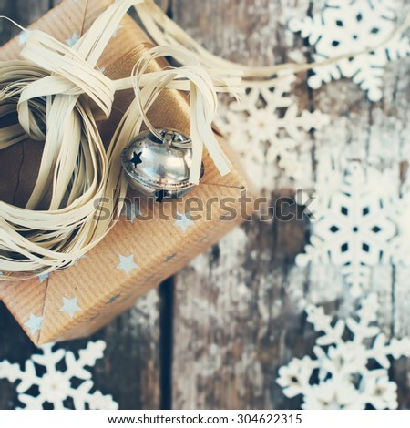 Christmas Card with Holiday Box, Jingle Bell and Natural Twine on Wooden Snow Background. Toned image - stock photo