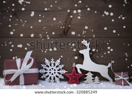Christmas Card With Red Festive Decoration On White Snow. Gift, Present, Reindeer, Christmas Ball, Christmas Tree, Snowflakes. Rustic, Vintage, Brown Wooden Background. Copy Space For Advertisement - stock photo