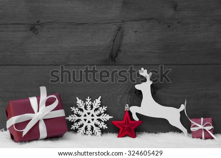 Christmas Card With Red Festive Decoration On White Snow. Gift, Present, Reindeer, Christmas Ball, Snowflakes. Brown, Rustic, Vintage Wooden Background. Copy Space For Advertisement. Black and White - stock photo