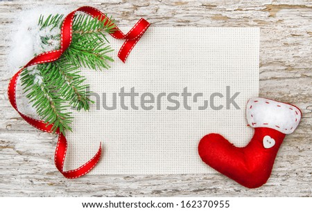 Christmas card with red sock, ribbon and fir branch  - stock photo