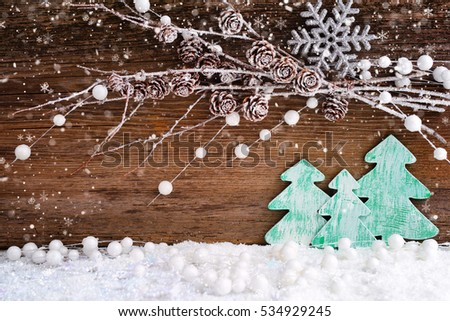 Christmas card with wooden christmas trees on the snow on a wooden background. Festive Christmas background