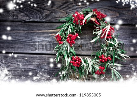 Christmas card with wreath,red berry on a rustic wooden wall with copy space and  snow/ holidays background - stock photo
