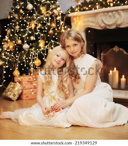 Christmas, celebration and people concept - happy family, mother and child near christmas tree and fireplace - stock photo