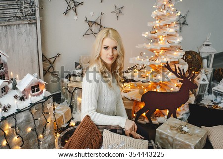 Christmas celebration. Beautiful young woman stands in a room decorated for Christmas and smiles.