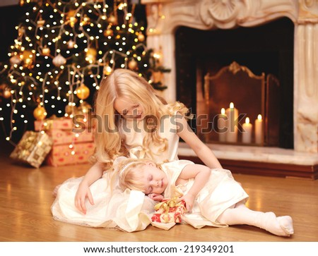 Christmas, celebration, holiday, xmas concept -  little girl gives a gift to his sleeping sister - stock photo