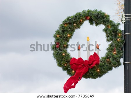 christmas chaplet decoration on a light pole with a red bow