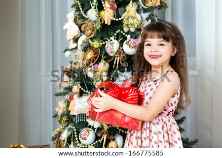 Christmas. Cheerful little girl holding a gift box and smiling