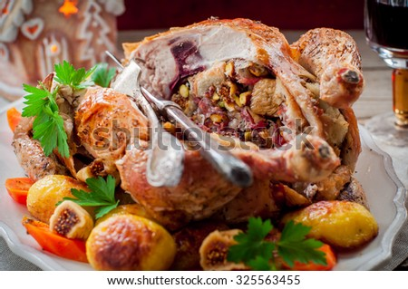Christmas Chicken Stuffed with Bacon, Pistachio, Fig and Bread Served with Potatoes and Carrots - stock photo