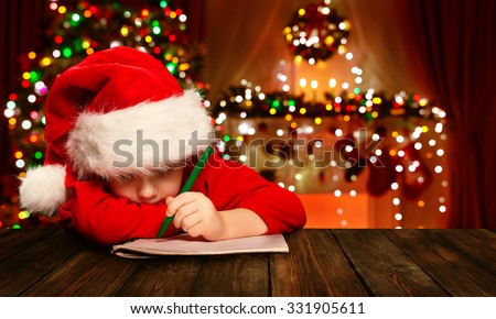 Christmas Child Write Letter to Santa Claus, Kid in Santa Hat Writing Wish List, unfocused lights background - stock photo