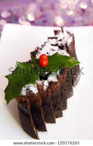 Christmas chocolate pudding on a white plate - stock photo