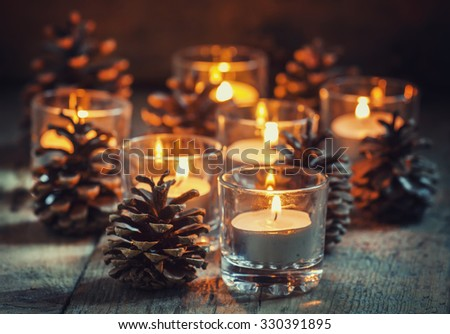 Christmas Christmas card with glowing small candle and fir cones on old wooden background, dark toned image in country style, selective focus - stock photo