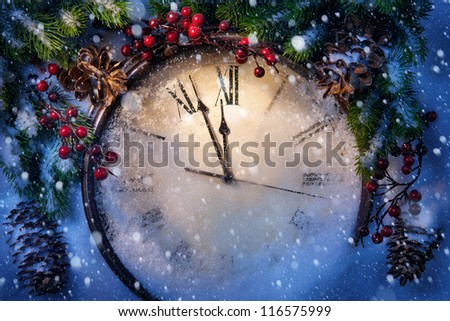Christmas clock and fir branches covered with snow - stock photo