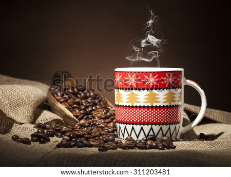 Christmas coffee cup and coffee beans on burlap textile and brown background. - stock photo