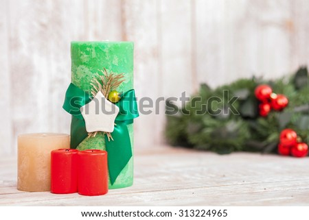 Christmas colored candles are congratulating people on the occasion. There is Christmas pine wreath with red toys on the background - stock photo