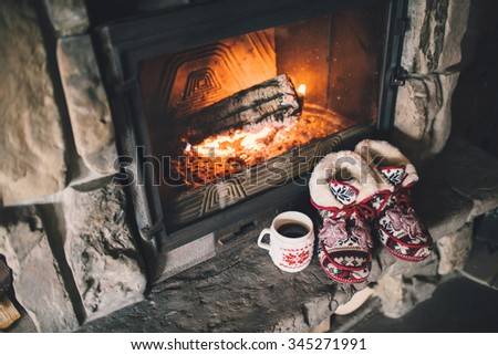 Christmas comfortable slippers by the warm cozy fireplace. Relaxing atmosphere in a chalet by authentic vintage fireside with a cup of hot drink. Winter and Christmas holidays concept. - stock photo