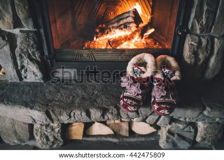 Christmas comfortable slippers by the warm cozy fireplace. Relaxing atmosphere in a chalet by authentic vintage fireside. Winter and Christmas holidays concept - stock photo