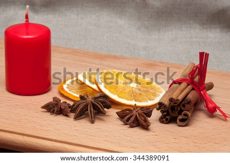 Christmas composition candle, dried orange, anise, cinnamon. on wooden background - stock photo