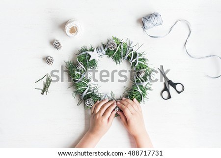 Christmas composition. Child making handmade christmas wreath. Top view, flat lay
