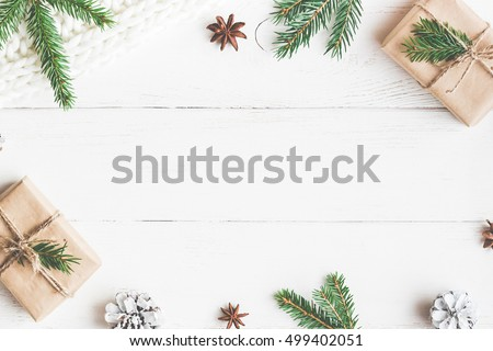 Christmas composition. Christmas gift, knitted blanket, pine cones, fir branches on wooden  white background. Flat lay, top view