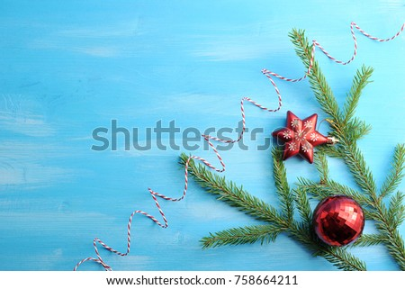 Christmas composition from a spruce branch, a red ball, a red six-pointed star and a red packing tape. Blue wood background. View from above. Close-up. Free space for text.