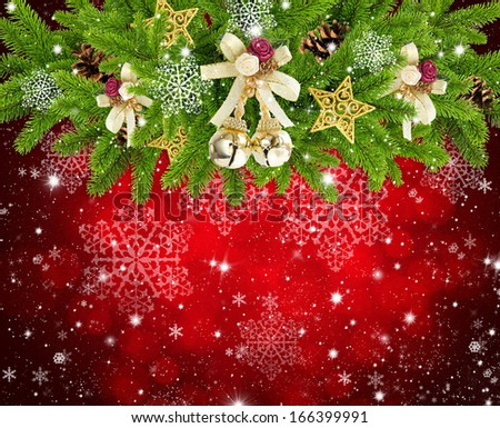 Christmas composition is with the branches of spruce and by decorations on festive red background - stock photo