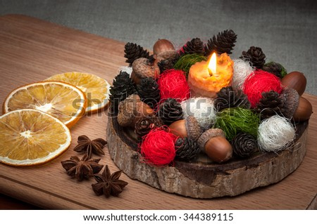 Christmas composition â?? lit candle wax, cones, acorns, balls, dried orange, anise. - stock photo