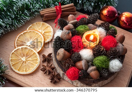 Christmas composition - lit candle wax, cones, acorns, balls, dried orange, anise, cinnamon. On wooden background. - stock photo