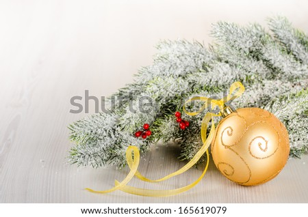 Christmas composition of fir--tree and golden bauble on light wooden background - stock photo