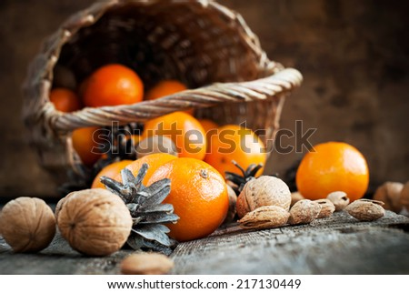 Christmas Composition with Basket, Nuts and Food. Tangerines, Pine cones, Walnuts, Almonds are scattered on wooden background. Rural style. Russian tradition - stock photo