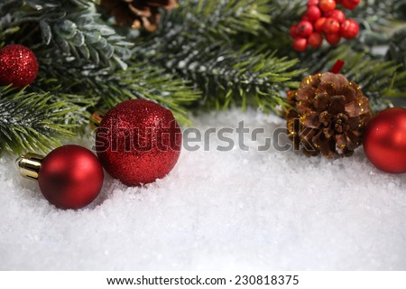 Christmas composition with baubles and fir-tree on snow close-up - stock photo