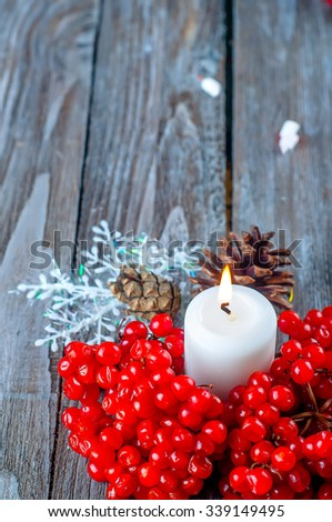 Christmas composition with candles and viburnum on wooden background