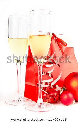 Christmas composition with champagne and paper bag in red colors on white
