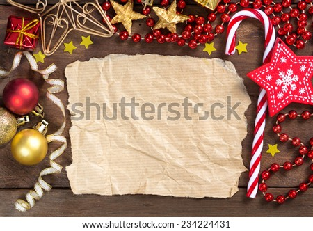 Christmas composition with decorations and paper on wood - stock photo