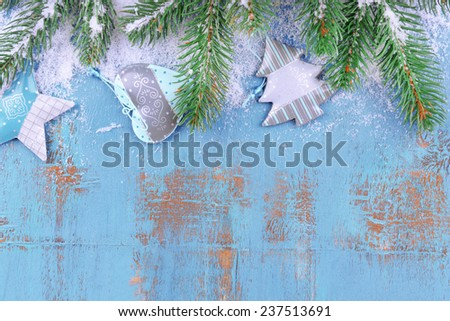 Christmas composition with fir tree with toys and snow on wooden background - stock photo