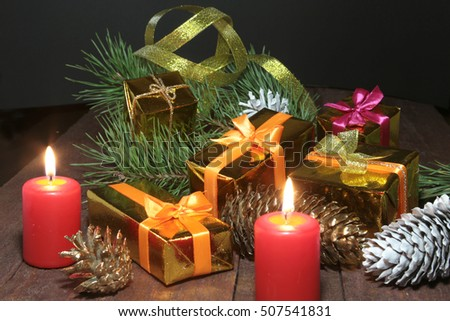 Christmas Composition with glass cognac, Gift box and candle on wooden table.